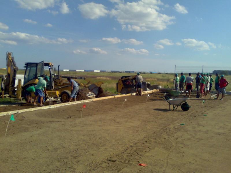 Manipulare mecanizata a adaosului de pamant si manuala pamant, nisip, pietris pentru nivelarea suprafetelor de gradina.