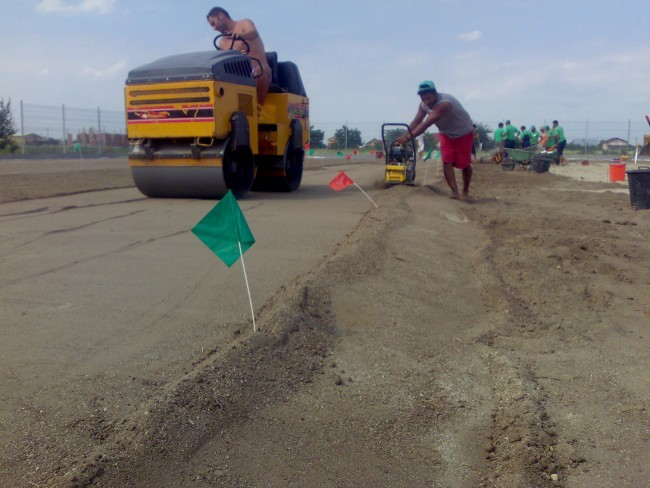 Imprastiere, nivelare si compactare succesiva a straturilor de pamant fertil amestecat cu nisip pentru realizarea unei suprafete stabile de joc