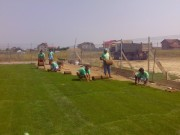 Rulouri de gazon montate pe teren de fotbal cu suprafata pregatita pentru instalarea gazonului rulat
