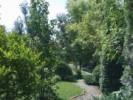 Amenajarea peisagistica a unei gradini medii cu plante ornamentale de gradina, alei, elemente decorative si gazon.